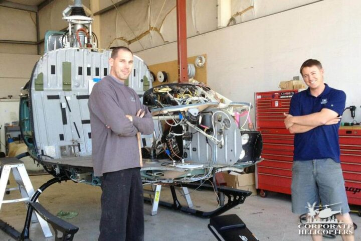 Two mechanics pose during a 12-year helicopter inspection