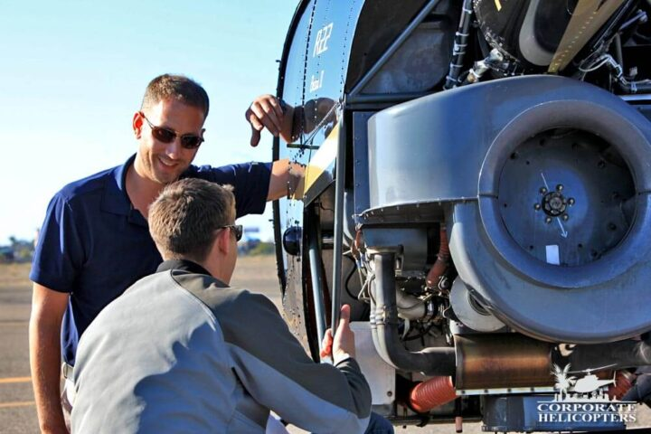 Flight training instructor and student inspect a helicopter