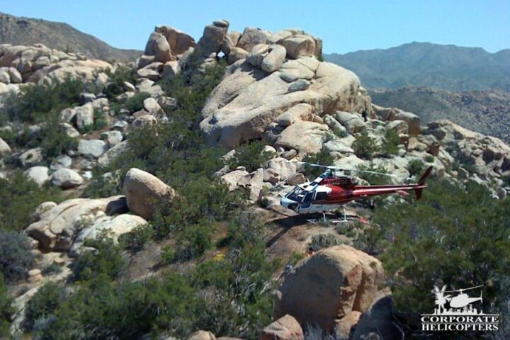 Helicopter landed on the side of a rocky Southern California mountain