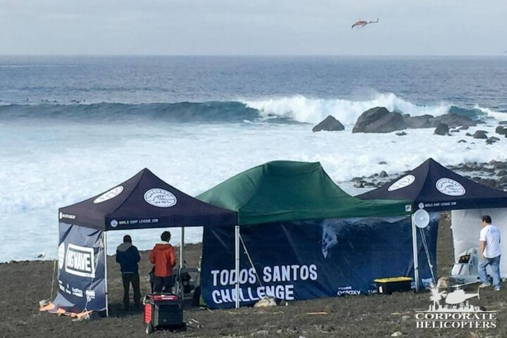 Specatators and event staff view a big wave at the Todos Santos Challenge as a helicopter flies in the distance