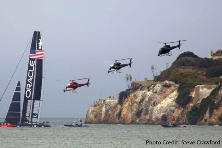 A large boat race and three helicopters