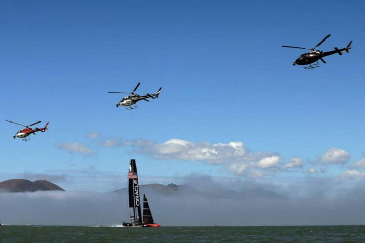3 helicopters flying over a boat