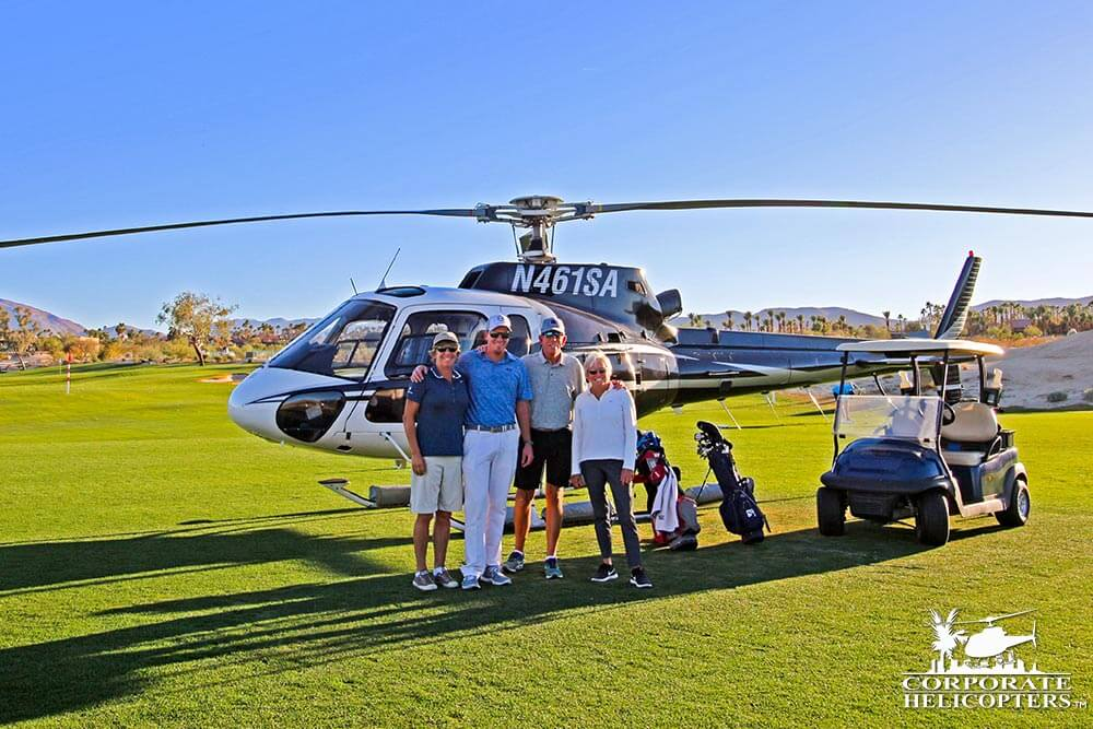 Group poses in front of helicopter on golf course