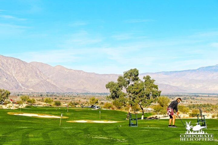 Woman about to tee off on golf course with helicopter in the background