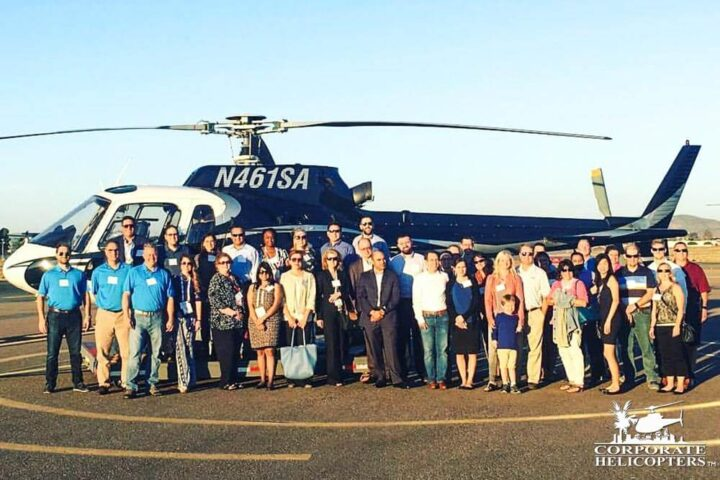 A large group poses of about 30 people in front of a helicopter