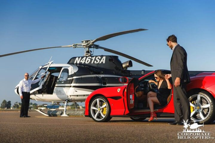 Man helps woman exit Porsche with helicopter waiting for them in the background