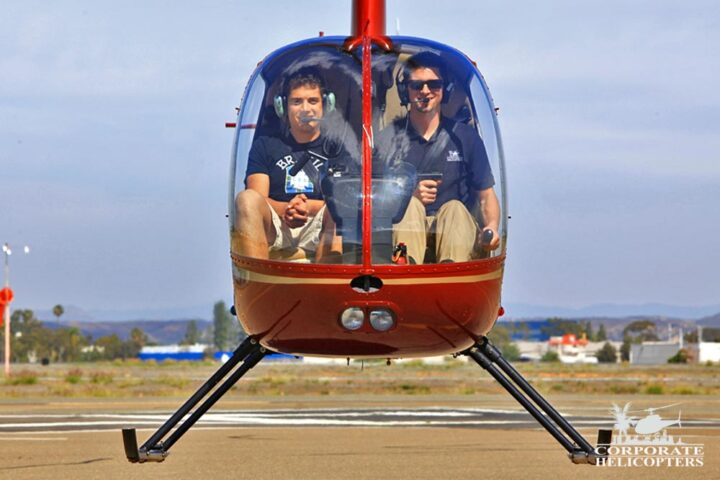 Two people in a helicopter. The helicopter is hovering inches from the ground.
