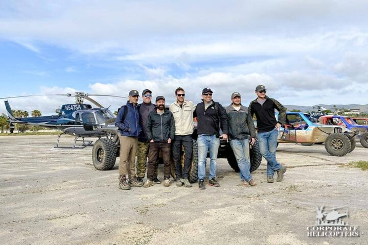 Off road race crews posing for photograph in front of race vehicles and helicopter