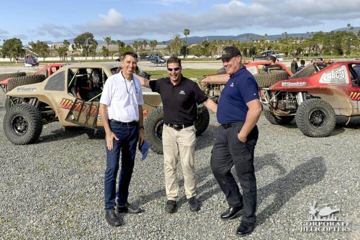 Three gentlemen in front of off road racing vehicles