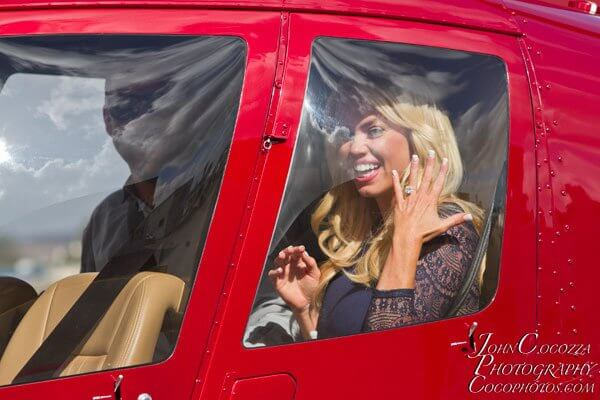 A newly engaged woman shows off her ring inside of a helicopter