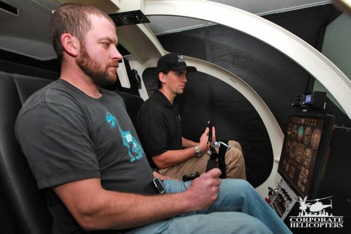 2 students inside of a helicopter flight simulator